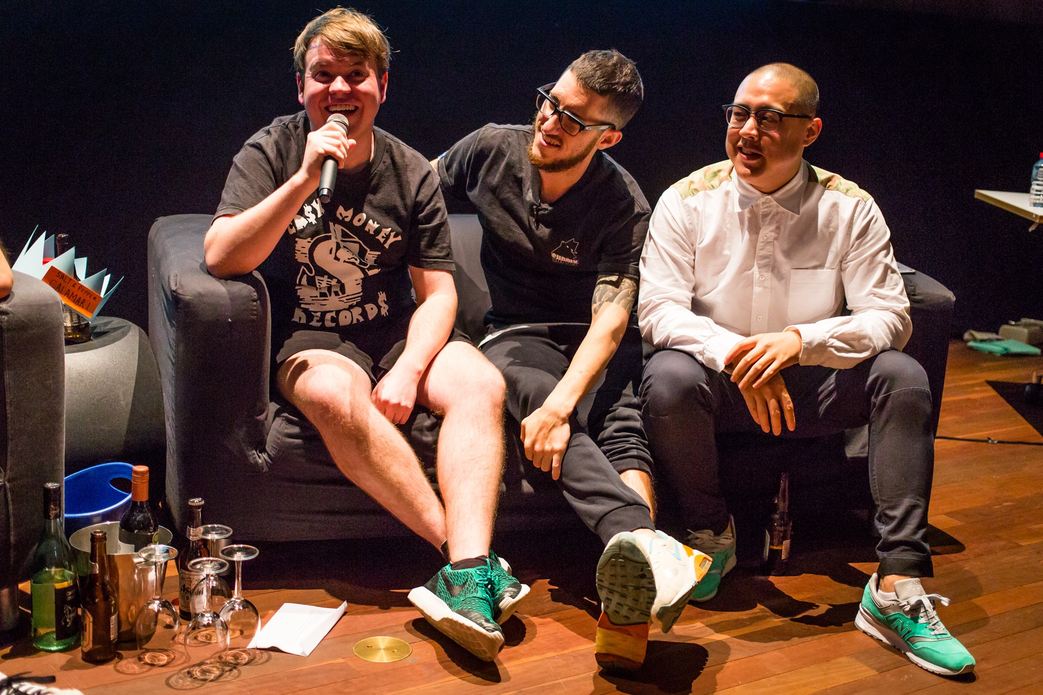 Three men on a couch, one is holding a microphone presenting a live podcast