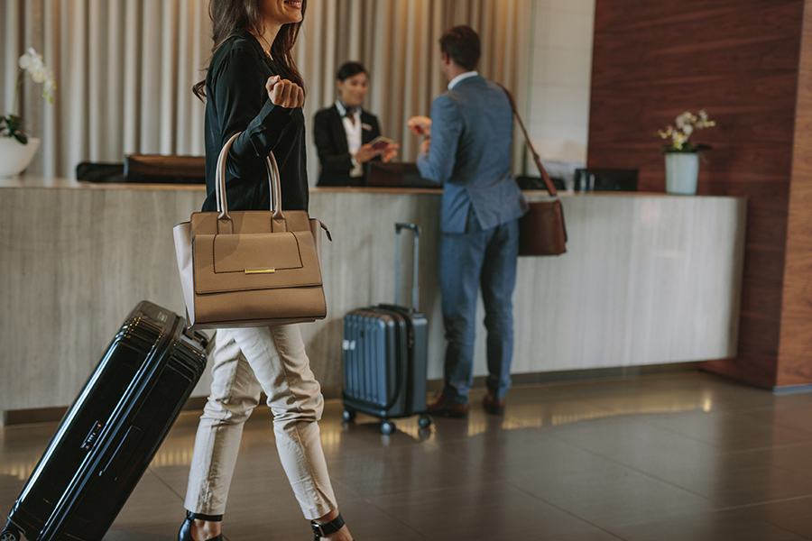 Woman carrying a handbag and suitcase in a hotel lobby
