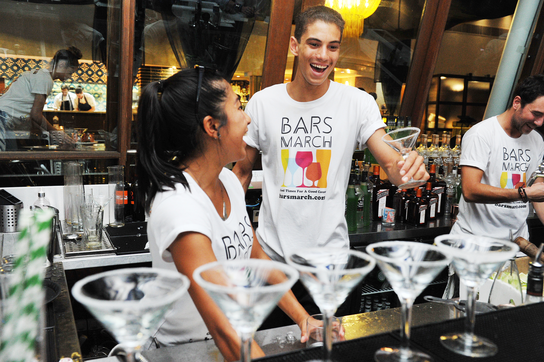 Two bartenders preparing a round of martinis at a bar