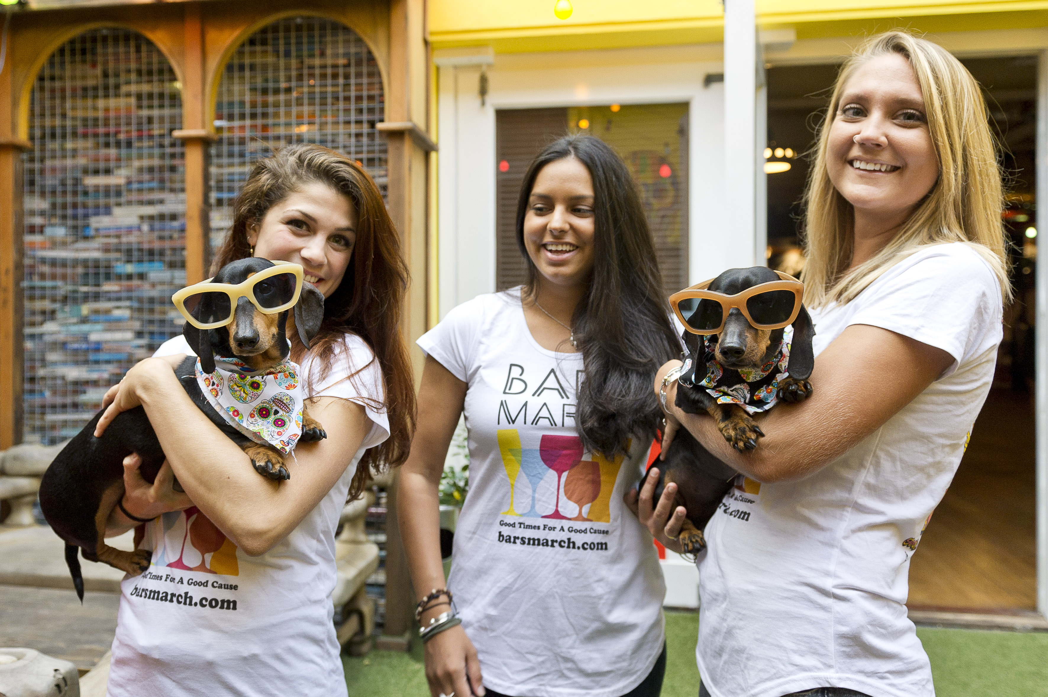 Three women, two are holding sausage dogs with oversizes sunglasses