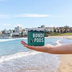A hand holds a box of Bondi Pods coffee capsules in front of the Bondi Beach coastine