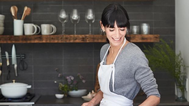 Host Kerry Diamond in a grey kitchen wearing an apron