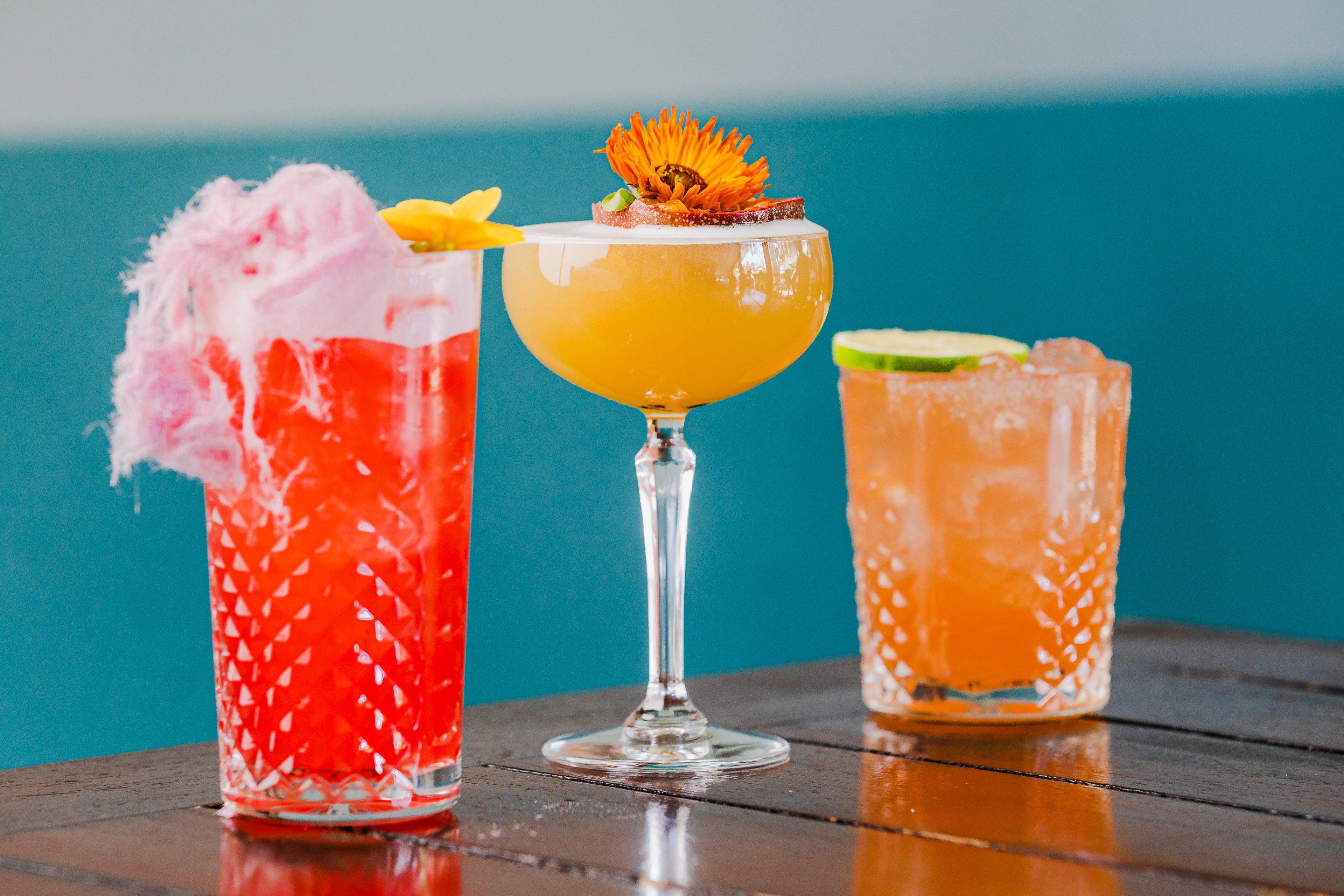 Three vibrant cocktails with an out of focus blue background